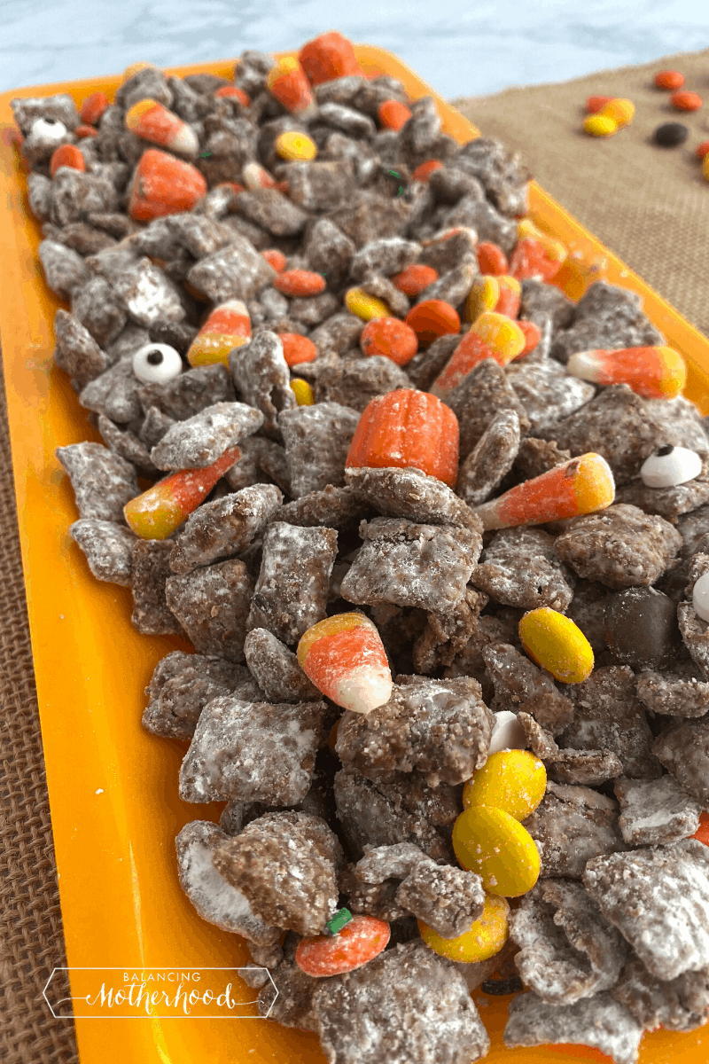 long plate with puppy chow on top showing pieces of Halloween candy throughout.