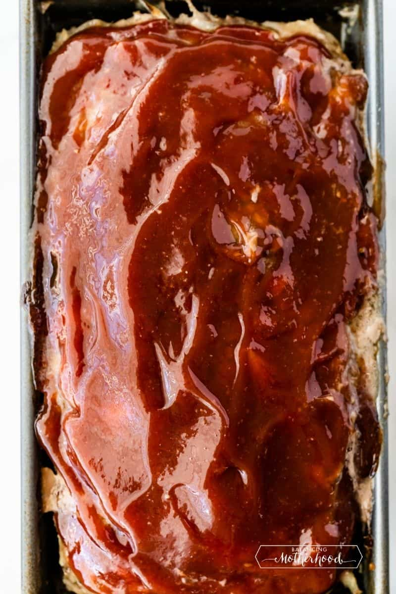 Top view of meatloaf in pan with red sauce on top.