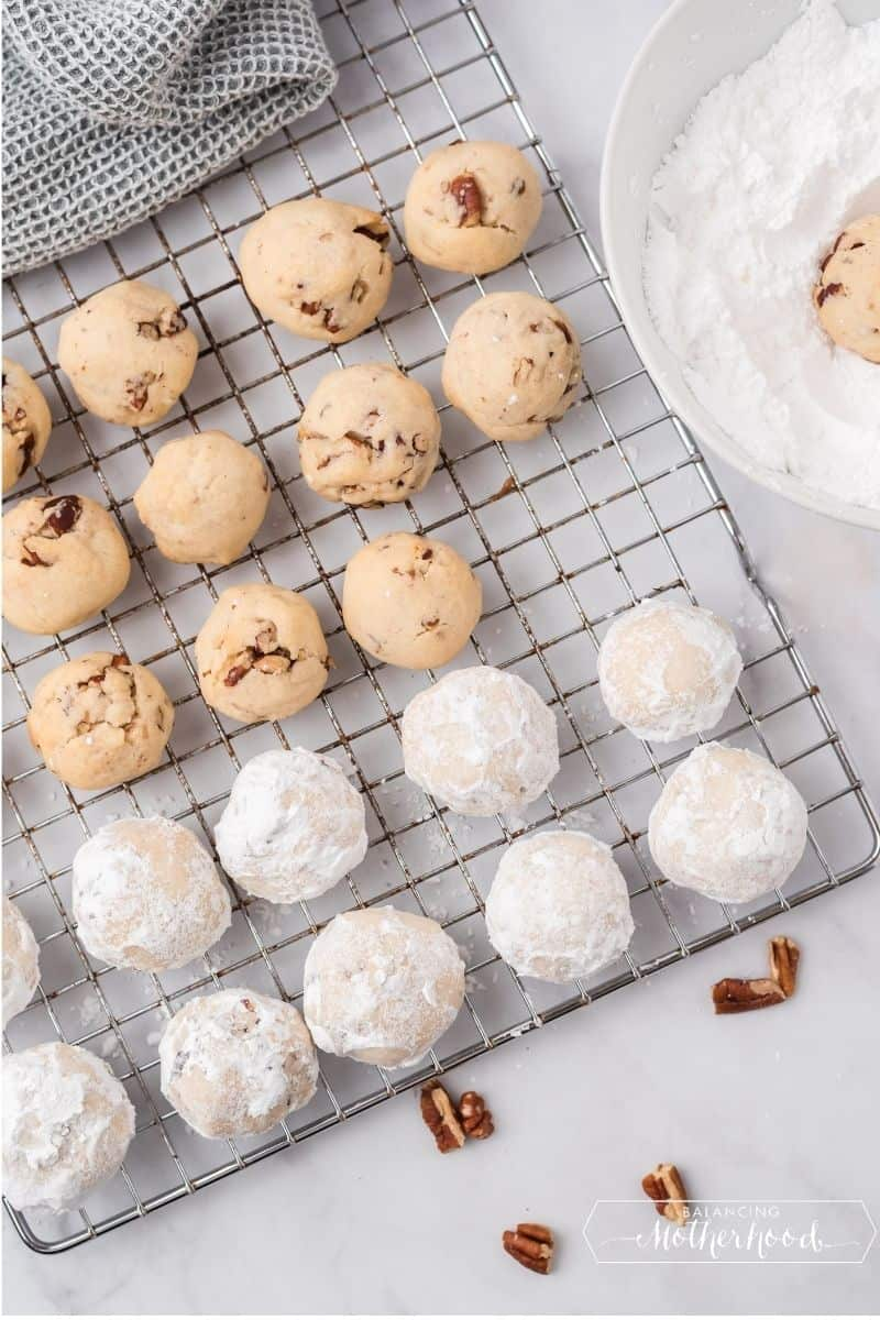 Baking rack with half rolled cookies, and half rolled in powdered sugar.