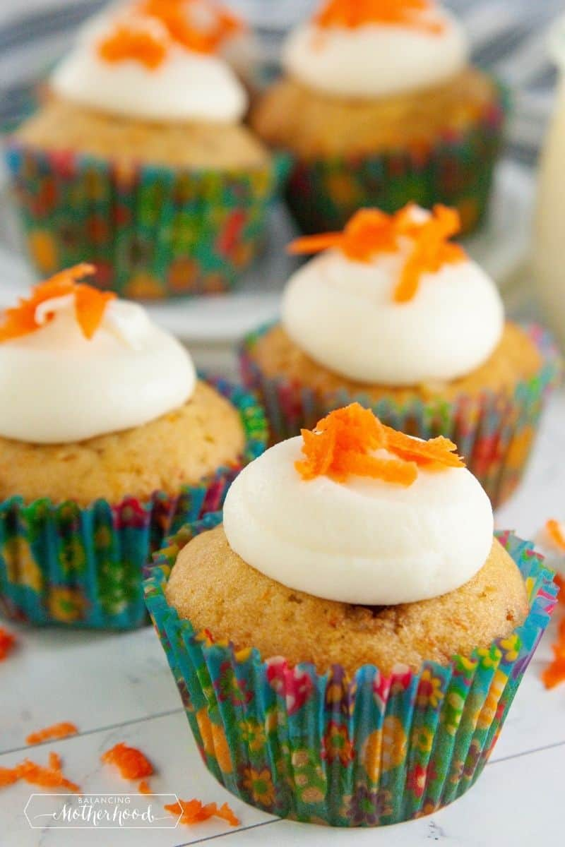 carrot cake cupcakes with a dollop of cream cheese frosting on top with shaved carrots for garnish