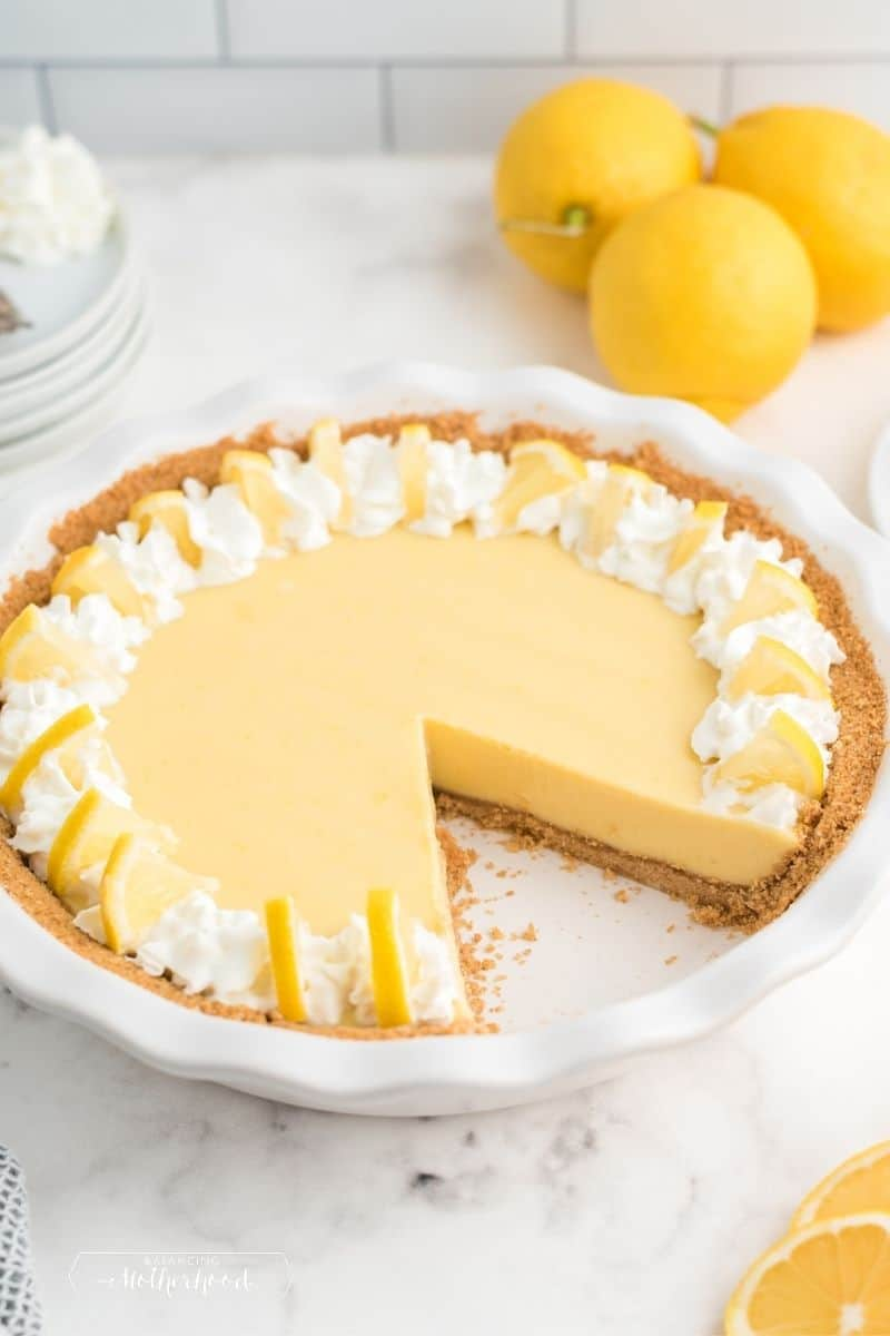 lemon pie with slice cut out with lemons in background