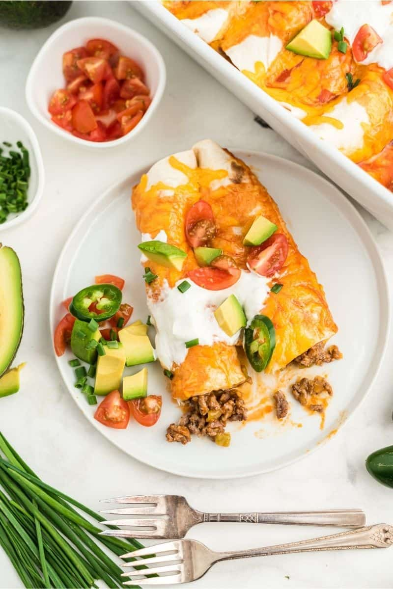 two enchiladas on plate with sour cream, tomatoes, and peppers on top, two forks on the side