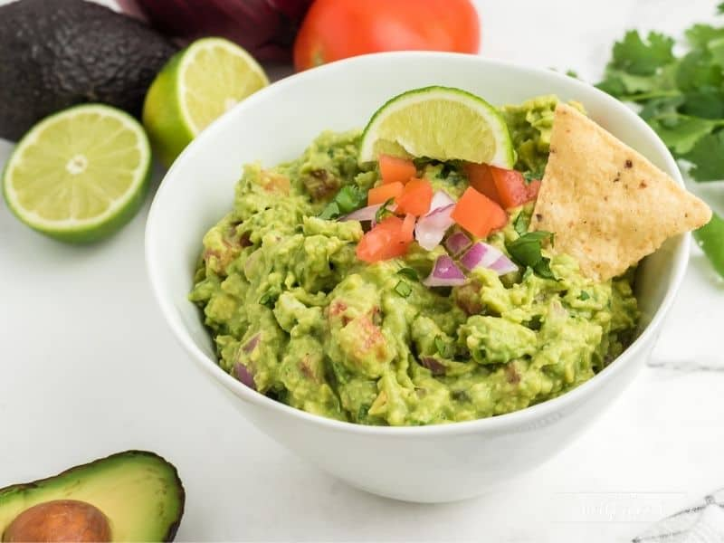 white bowl with guacamole topped with lime slice, diced tomatoes and onion with two chips