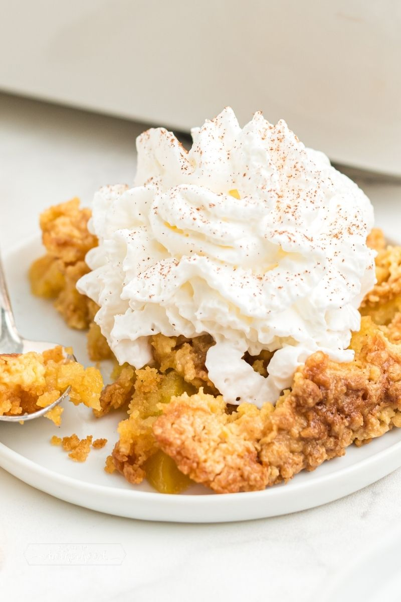 peach dump cake on white plate with whipped cream and cinnamon