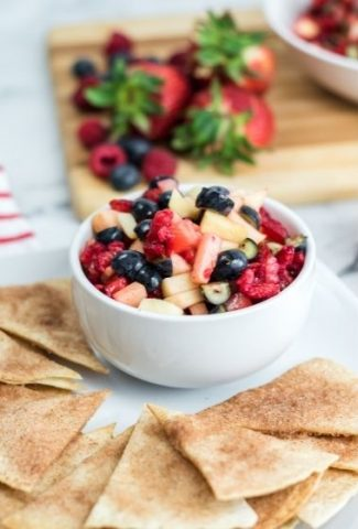 white bowl with fruit salsa and strawberries in background