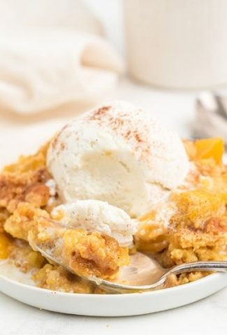 peach dump cake on white plate with spoon and topped with vanilla ice cream