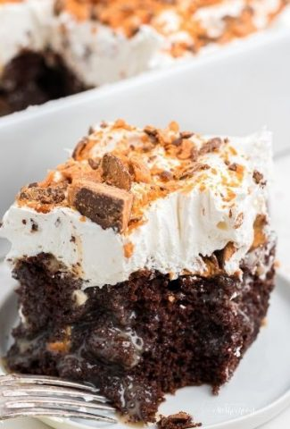square piece of chocolate cake with whipped cream and butterfinger candy pieces on top with fork on the side