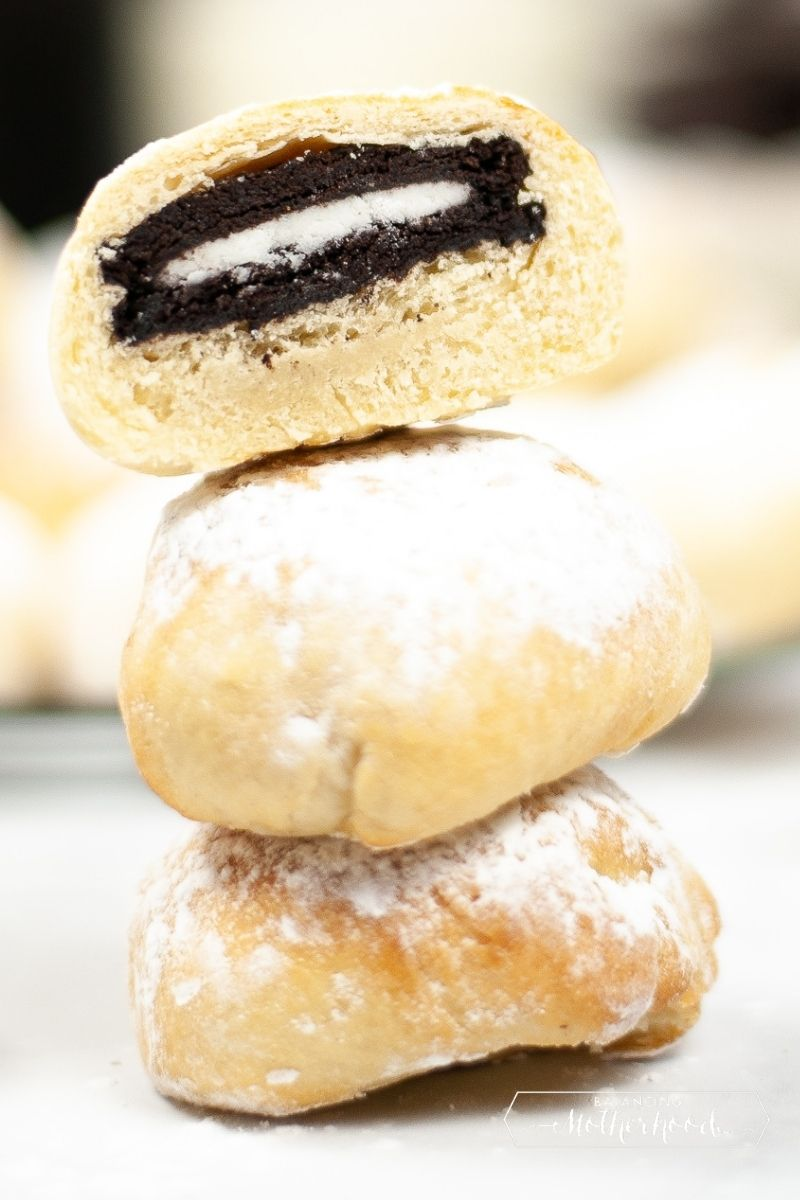 stacked air fried Oreos. Top one is cut in half showing the inside with an Oreo in the middle.
