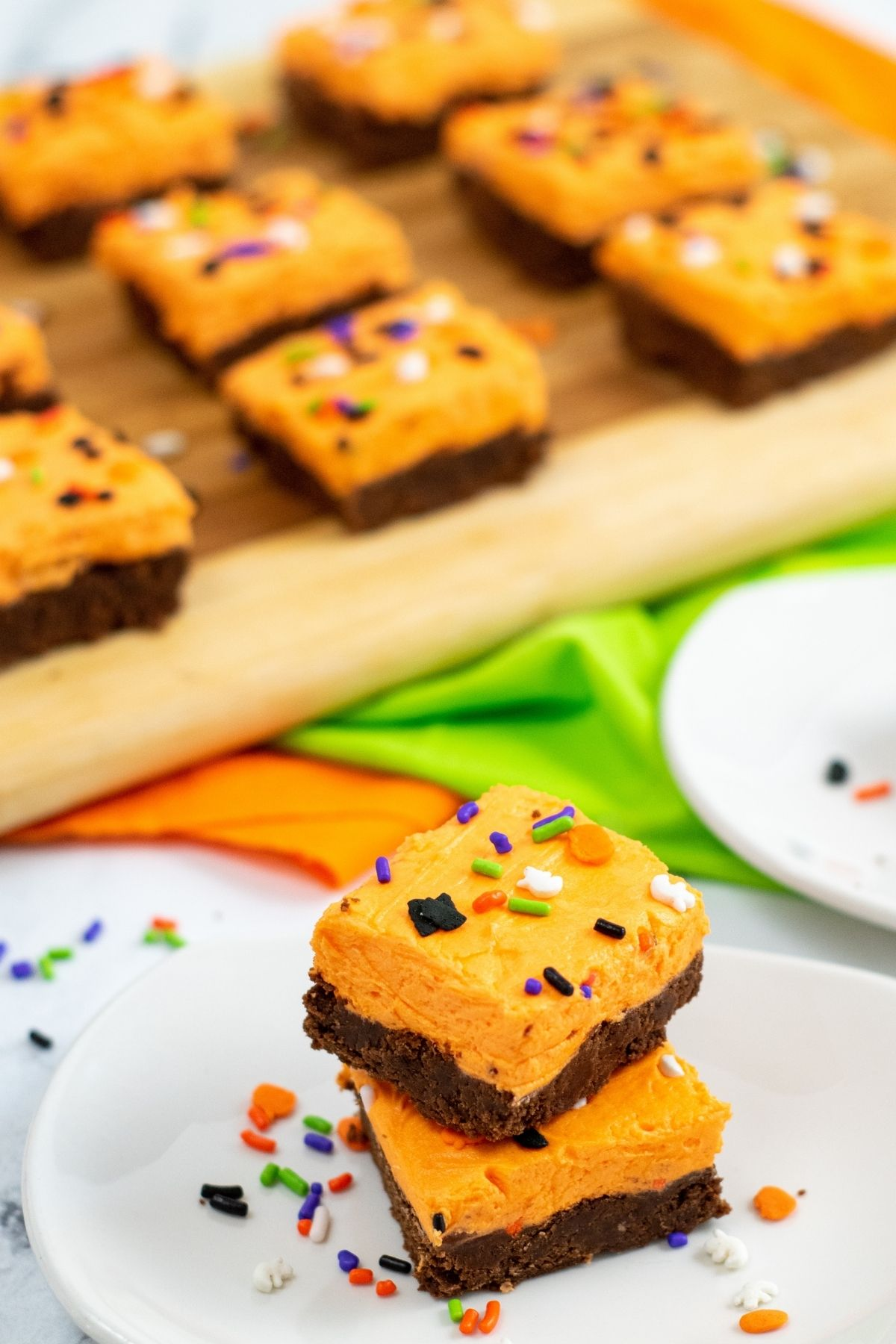 chocolate squares with orange frosting and Halloween sprinkles on cutting board