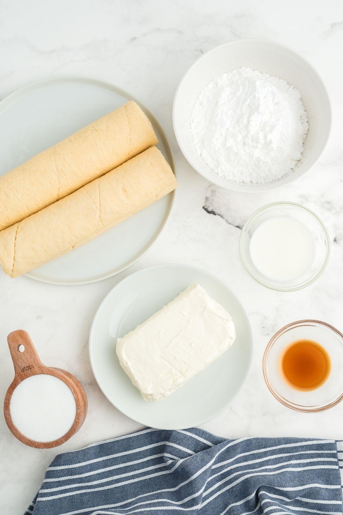 ingredients on white counter: 2 crescent rolls, powdered sugar, milk, vanilla, cream cheese, sugar