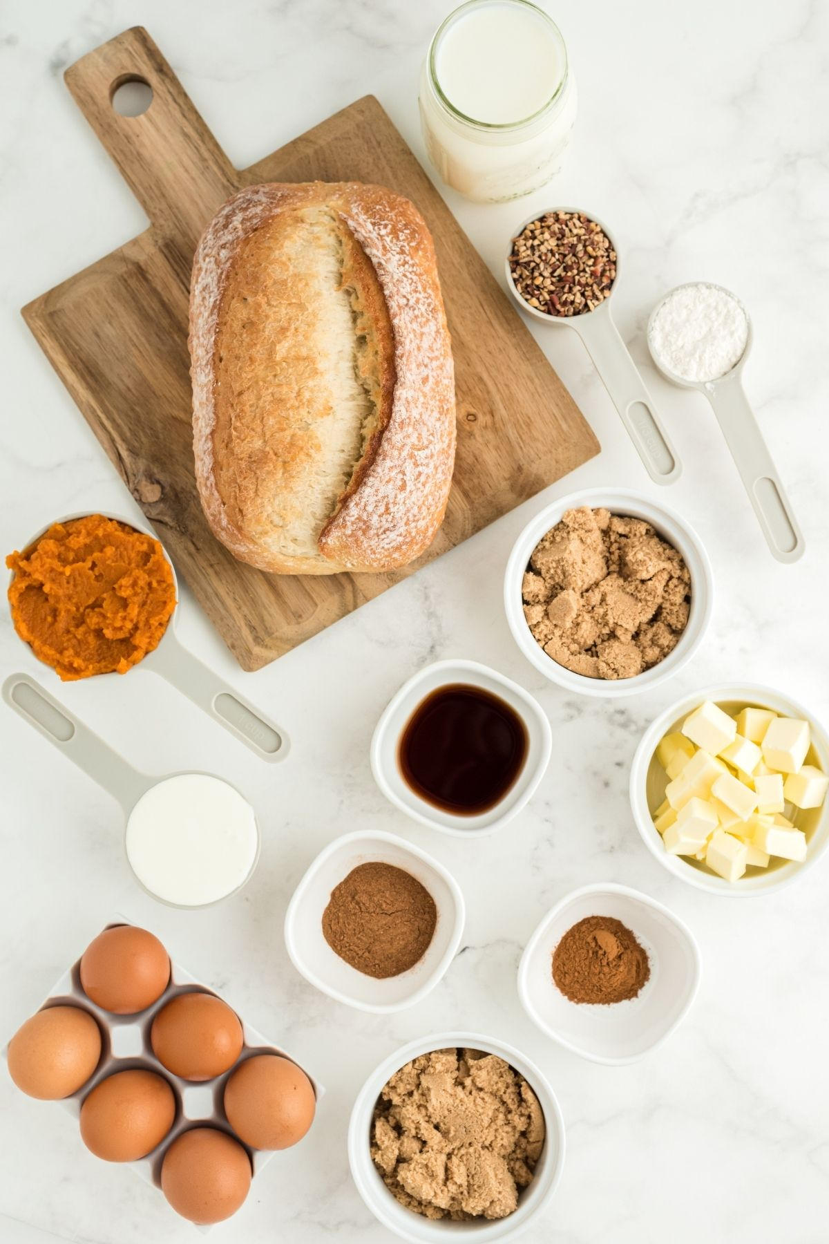 ingredients on white counter: loaf of crusty French bread, pumpkin puree, brown eggs, diced butter, vanilla, pumpkin pie spice, heavy cream, and milk
