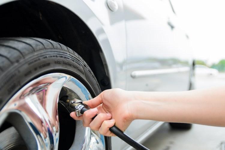 mão feminina fazendo a calibragem de um pneu