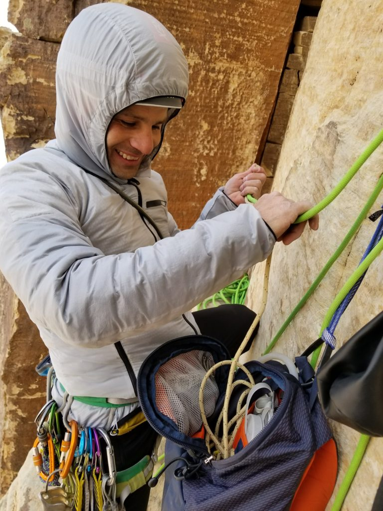 Marcus Garcia feeds rope into his Mutant 22 pack on a long climbing route in the Soutwhest.