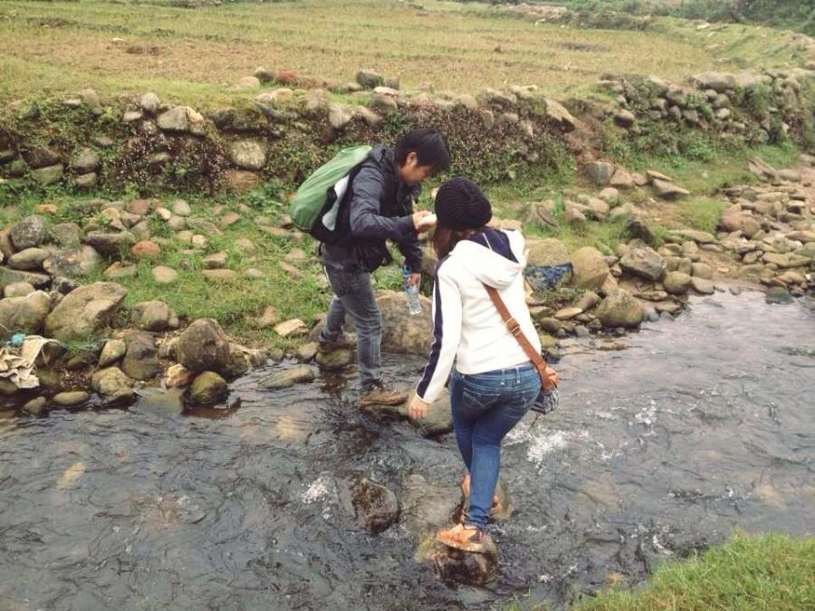 Hướng dẫn viên giúp mình vượt qua suối