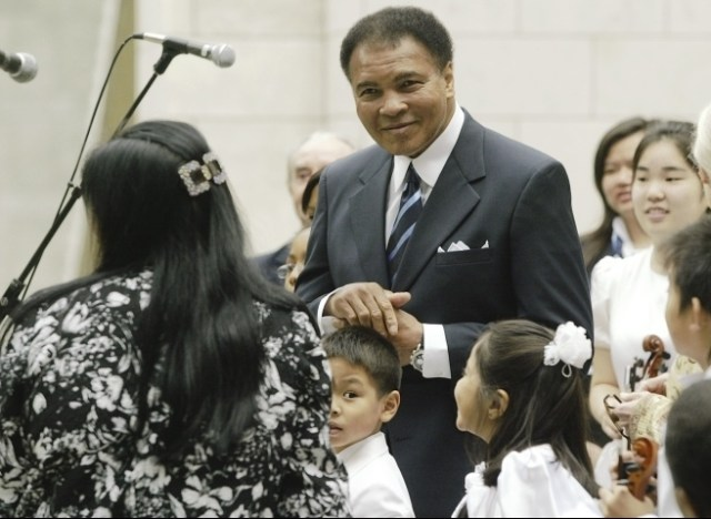 "Known as a motivator and inspiration to many, UN ""Messenger of Peace"" Muhammad Ali, enjoyed the violin performances of the Tarumi Violinists, under Yukako Tarumi, shown on the far left, on the International Day of Peace, September 21, 2004. UN Photo/Ky Chung."