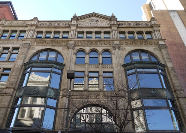 The upper stories of an ornately-detailed department store building faced in light gray stone with large windows.