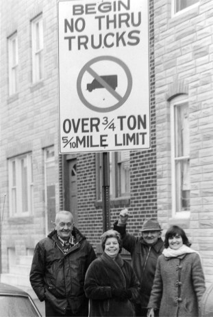 Harry Warren Lowe on far left, SBIC members in center, and Carol Lowe on far right, all sanding under sign erected  as a result of their advocacy.