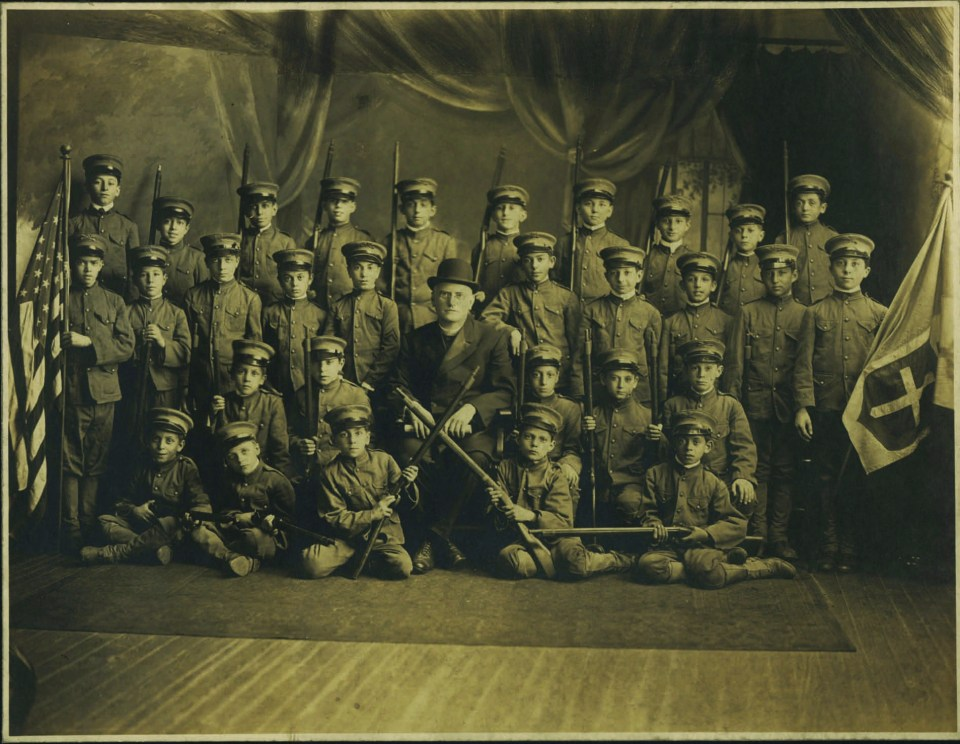 "A group picture of the cadet club of St. Leo's Church. Angelo Pente, here a young boy (seated third row from the top, far right), wrote later in life that they used the church basement as their training ground, remarking ""it kept the youths out of trouble."""