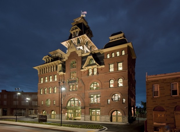 A nightime view of a large Victorian brick building with light shining from the windows.