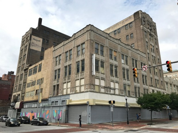 A large multi-story vacant department store building at the corner of two streets.