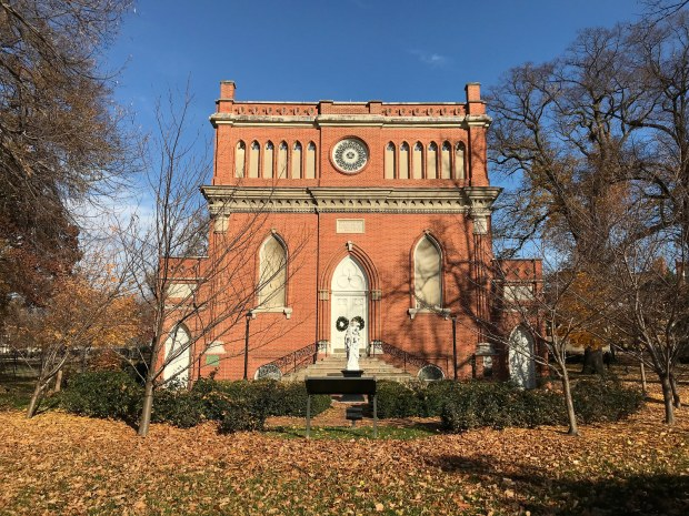 A Gothic brick chapel in a park.