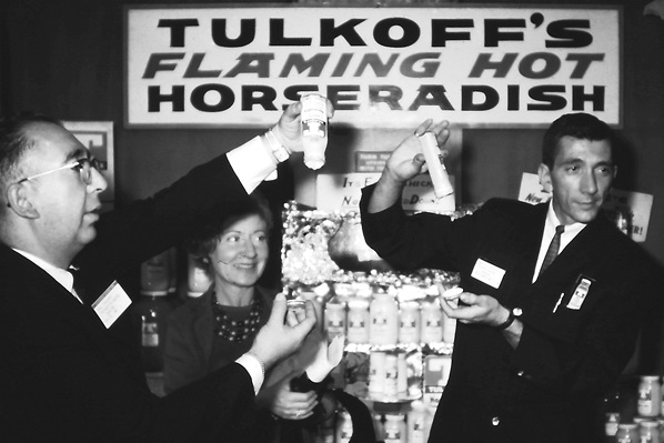 Black-and-white photo of three people holding bottles of Tulkoff's flaming hot horseradish.