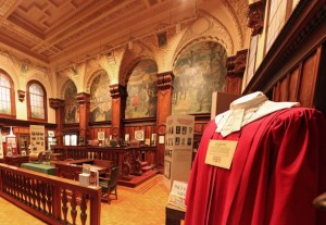 Courtroom with rich mahogany wood and finely painted walls and ceiling.
