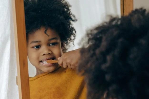 petite fille qui se brosse les dents avec brosse a dents en bambou