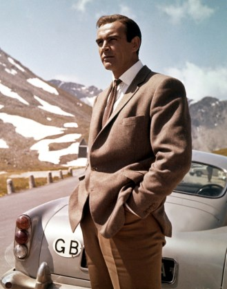 Sean Connery as James Bond stands behind his Aston Martin DB5 while filming Goldfinger.