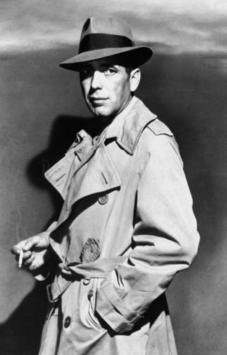 Humphrey Bogart models his Borsalino fedora and personal Aquascutum trench coat to promote Casablanca (1942), though he would wear a different Burberry coat on screen.