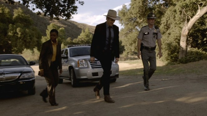 """Raylan bridges the gap between Rachel's professional U.S. Marshal duds and the Kentucky state trooper's more traditional uniform in """"The Moonshine War"""" (Episode 2.01), although neither Rachel nor the trooper have the gumption to pull off a pair of ostrich leg boots."""