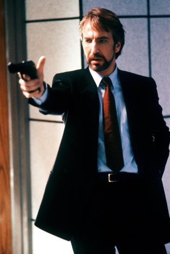 Hans Gruber (Alan Rickman) aims John McClane's own Beretta at him in a production still from Die Hard (1988).