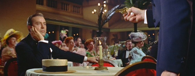 White coolly sits with his hat on his table when Harry Thaw approaches him with his gold revolver drawn.