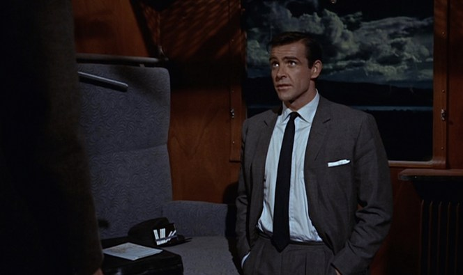 Note the usual double forward pleats and beltless waistband of Bond's Sinclair-tailored trousers.