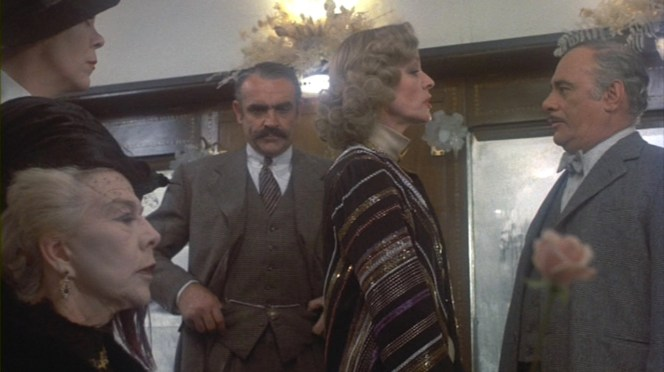 Arbuthnot stands pensively behind Mrs. Hubbard (Lauren Bacall) as she gets the scoop from Bianchi (Martin Balsam).