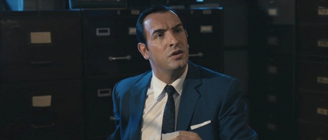 OSS 117 is confronted by a revolver-wielding Raymond Pelletier.