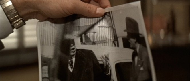 Gittes' watch bracelet gleams while he looks over his team's surveillance photos of Noah Cross and Hollis Mulwray.