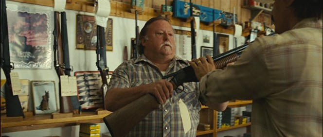 Considering that he actually pays for the weapon and doesn't draw a pistol on him, Llewelyn Moss is much nicer to this store clerk than McQueen was in The Getaway.