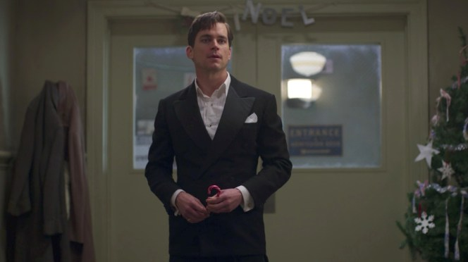 """An exhausted Monroe Stahr stands in his black tie kit, sans the actual tie, among hospital holiday decorations in """"A Brady-American Christmas"""" (episode 6)."""