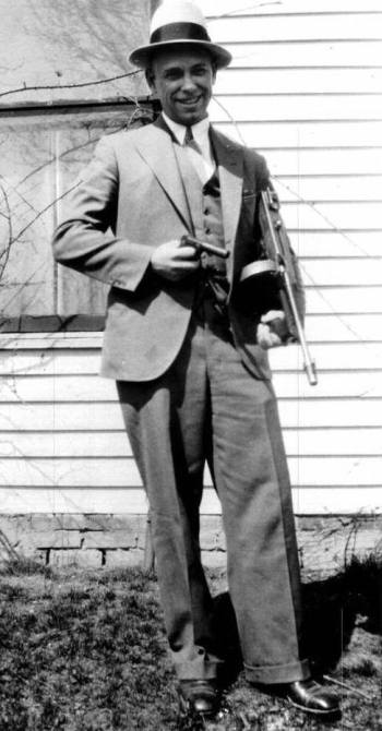 The real John Dillinger, posing at his family's home in Mooresville, armed with a wooden gun and a more lethal Thompson submachine gun. The date is Sunday, April 8, 1934, the day before girlfriend Billie Frechette would be arrested before his eyes in Chicago.
