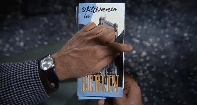 Armstrong flips through a pamphlet welcoming him to Berlin.