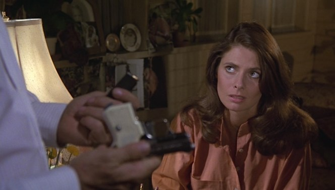 The Beretta Jetfire's white plastic grips are visible as Papa demonstrates how to reload the magazine for his dubious girlfriend Dottie (Kathryn Harrold).