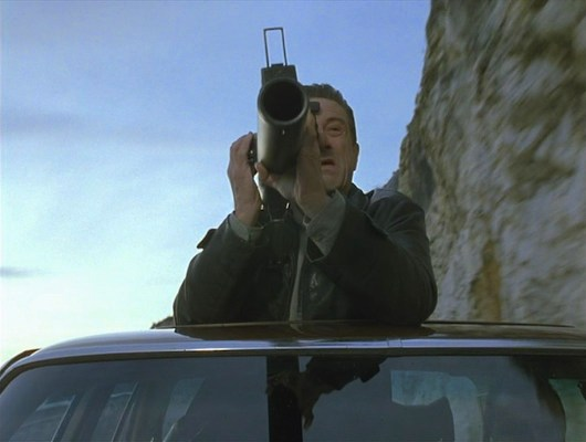 There's badass... and then there's Robert De Niro firing a rocket launcher from the open sunroof of a speeding Mercedes.