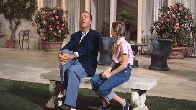 Bing in mid-croon, sporting his navy blazer, open-neck gingham shirt, and light blue-gray trousers.