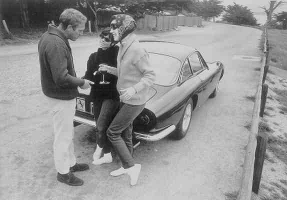 What's a road trip without refreshments? Peggy Moffitt enjoys a glass of wine while chatting with Steve and Neile. Note the actor's snazzy Ferrari. (Photograph by William Claxton, 1964)