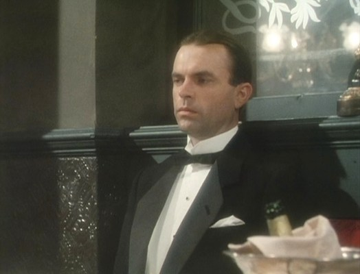"""Reilly sports a black wool notch-lapel dinner jacket for an evidently serious dinner with his friend and lawyer, Sasha Gramaticoff. The white pocket square only appears in """"Dreadnoughts and Doublecrosses"""" (Episode 6)."""