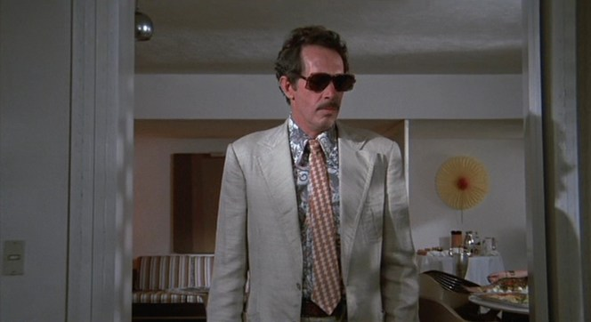 In his wrinkled linen suit, loud paisley shirt, and clip-on tie, Bennie dresses to impress when taking a job for the mob.