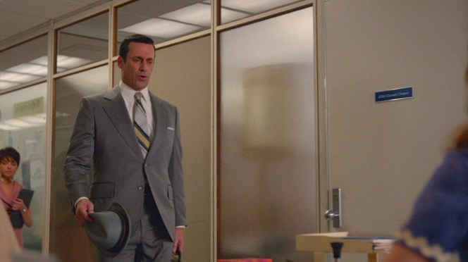 "Summer hat in hand, Don strolls up to his office at SC&P in ""The Forecast"" (Episode 7.10)."