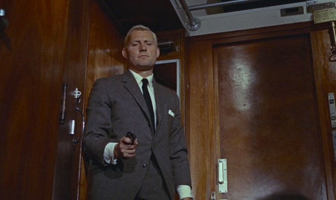 The gig is up. Grant keeps his gun drawn as he approaches a now-unconscious Bond.