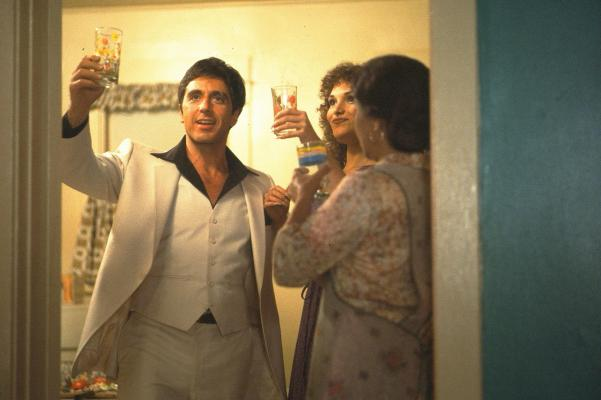 Production photo of Tony raising a toast with his sister Gina (Mary Elizabeth Mastrantonio) and their mother (Míriam Colón).